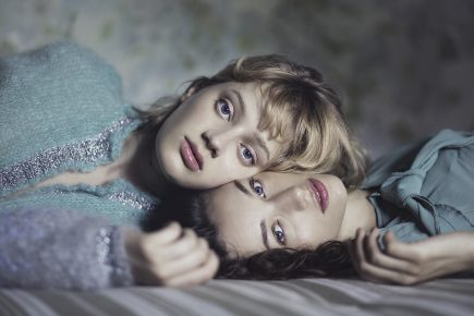 "alt=""two girls lying on bed"""