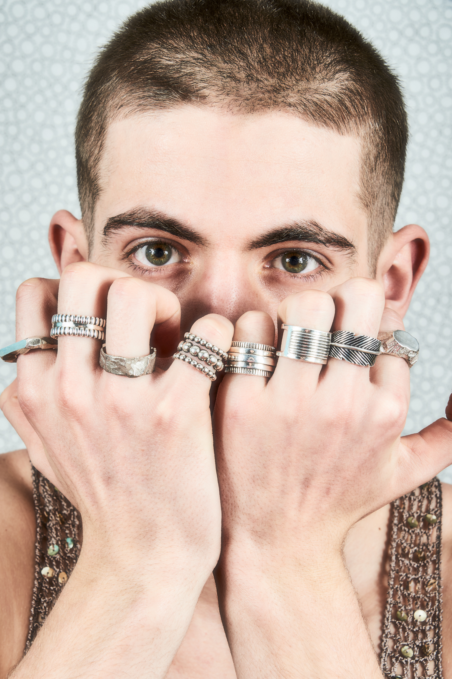 """Portrait of boy with hands full of rings on each finger"""