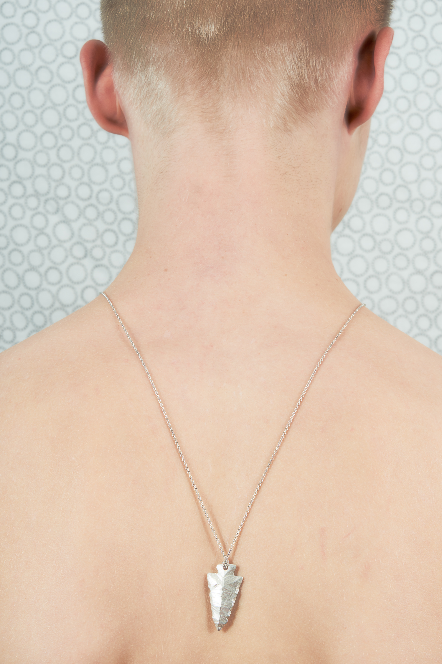 """Portrait of back of shaved guy with necklace"""